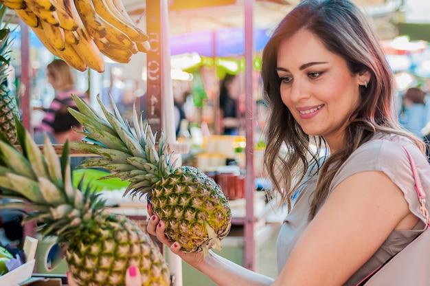 Attraktive frau einkaufen im grünen markt. closeup portrait schöne junge frau abholung, die wahl von früchten, ananas. positive gesichtsausdruck emotion gefühl gesund lebensstil Kostenlose Fotos