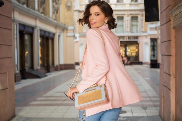 Attraktive frau im stilvollen outfit, das in der stadt, straßenmode, frühlingssommertrend, lächelnde fröhliche stimmung, rosa jacke und bluse, blick von hinten, eleganz, urlaub in europa geht Kostenlose Fotos