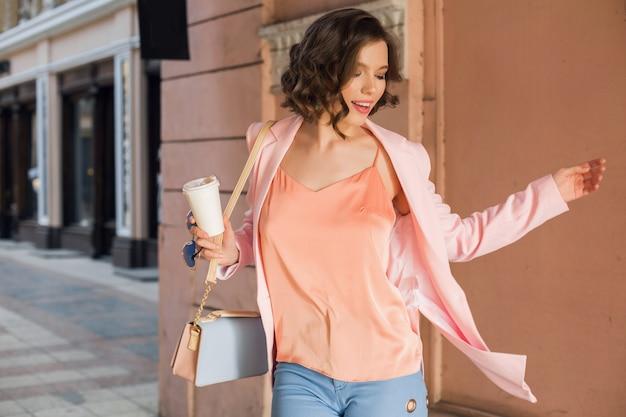 Attraktive frau im stilvollen outfit, das in stadt, straßenmode, frühlingssommertrend, lächelnde fröhliche stimmung geht, rosa jacke und bluse trägt, herumwirbelt, verlassen, fashionista beim einkaufen Kostenlose Fotos