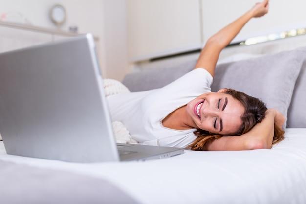 Attraktive frau im weißen hemd unter verwendung des laptops und lächeln am morgen. videochat und freiberuflich tätiges arbeiten vom hauptkonzept der schönen jungen frau mit laptop im bett Premium Fotos