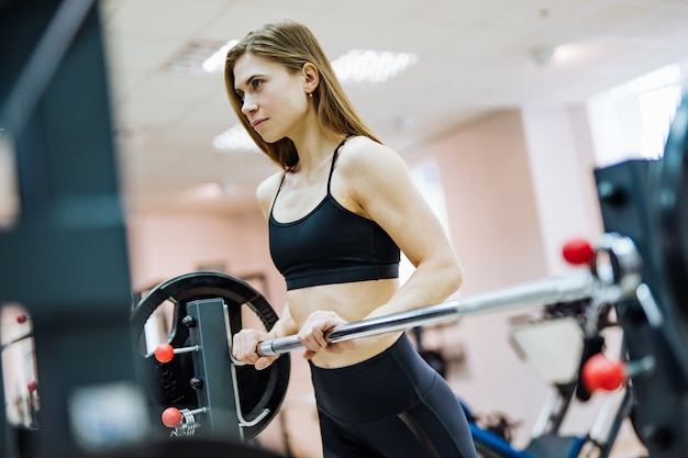 Attraktive frau in der schwarzen spitze und in den gamaschen steht an der hantelstange in der turnhalle. schlanke sportlerin trainiert im fitnesscenter und schaut nach vorn. Premium Fotos