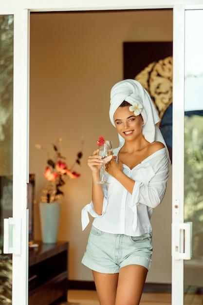 Attraktive frau in einem weißen bademantel und in einem tuch, die champagnerglas halten und die kamera lächeln. spa und resort Premium Fotos