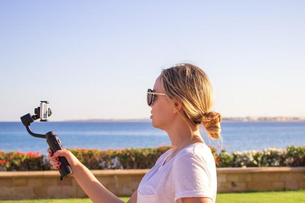 Attraktive frau zeichnet video mit modernem kardanischem 3d aufgehängtem kamera smartphone auf Premium Fotos