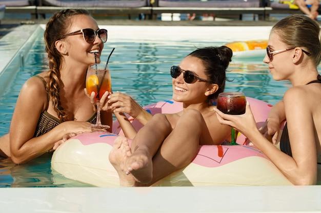 Attraktive frauen, die heißen sommertag am swimmingpool genießen Premium Fotos