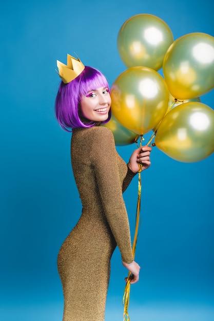 Attraktive freudige junge frau im modischen luxuskleid, die große party feiert. goldene luftballons, krone, geschnittenes lila haar, strahlendes make-up, lächeln, festtage. Kostenlose Fotos
