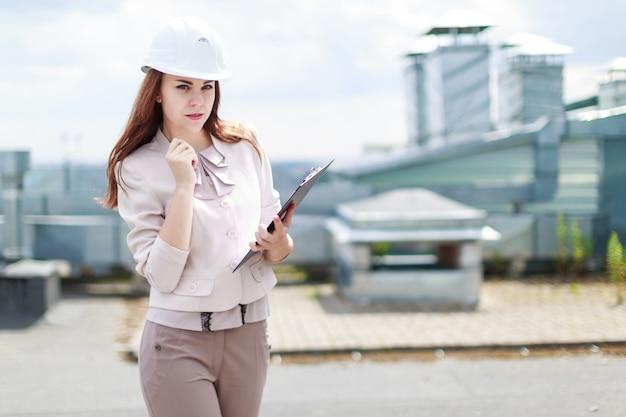 Attraktive geschäftsfrau im beige klagestand auf der dach- und grifftablette Premium Fotos