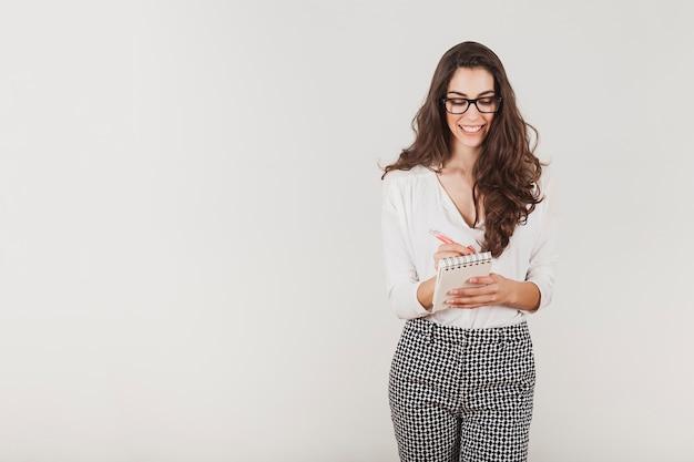 Attraktive geschäftsfrau mit brille schriftlich Kostenlose Fotos