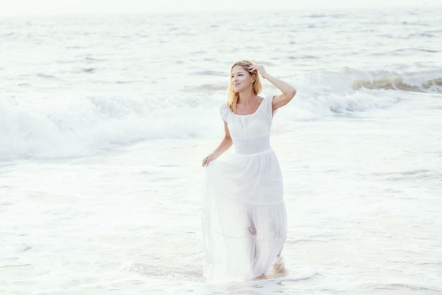 Attraktive glückliche reife touristische blondine im langen weißen kleid auf tropischem strand des asiatischen sandes. Premium Fotos