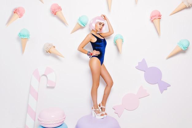 Attraktive hübsche sexy junge frau im bodysuit mit geschnittener rosa frisur, auf den fersen stehend auf riesigem macaron unter süßigkeiten. pastellfarben, genießen, süßer lebensstil. Kostenlose Fotos