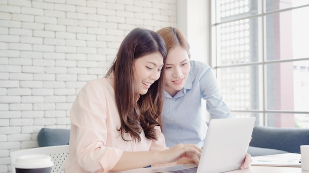 Attraktive intelligente kreative asiatische geschäftsfrauen in der intelligenten freizeitkleidung, die an laptop beim sitzen arbeitet Kostenlose Fotos