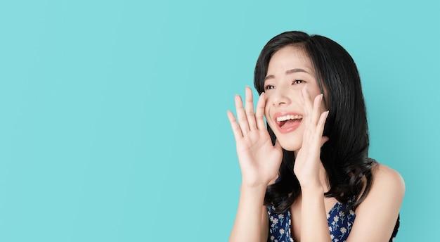 Attraktive junge asiatische frau, die mit den händen zum mund ankündigt und ein geheimnis erklärt. Premium Fotos