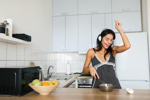 Attraktive junge dünne lächelnde frau, die spaß hat, eier in der küche am morgen zu kochen, frühstück im pyjama-outfit gekleidet, musik auf kopfhörern tanzend hörend Kostenlose Fotos