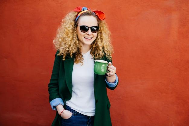 Attraktive junge europäische frau mit dem stirnband, das stilvolle jacke trägt. Premium Fotos