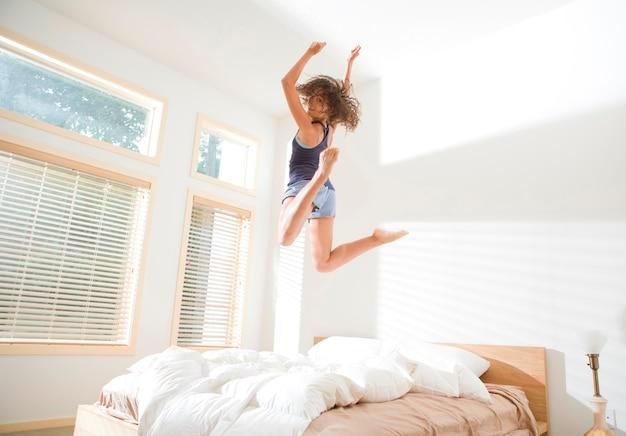 Attraktive junge frau, die auf bett springt und über schulter schaut Premium Fotos