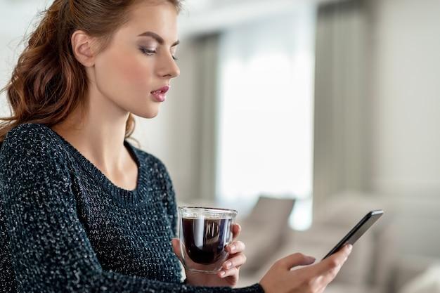 Attraktive junge frau, die ihr smartphone zu hause betrachtet. frau gibt nachricht auf ihrem smartphone ein. Kostenlose Fotos