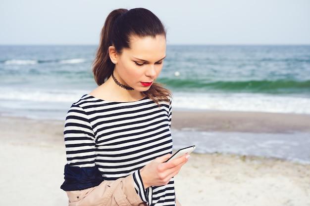 Attraktive junge frau, die in der hand entlang den strand mit einem intelligenten telefon geht Premium Fotos