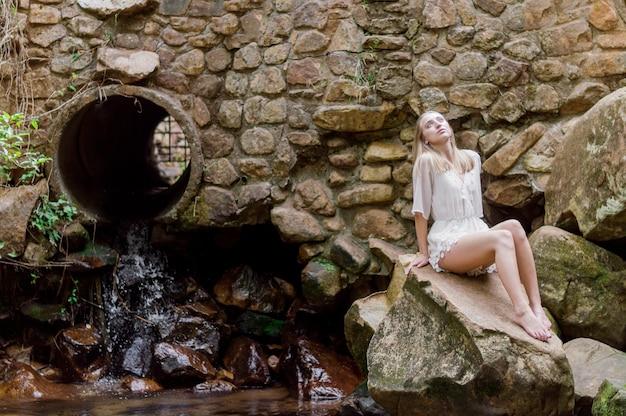 Attraktive junge Frau, die neben einem Rohr sitzt Kostenlose Fotos