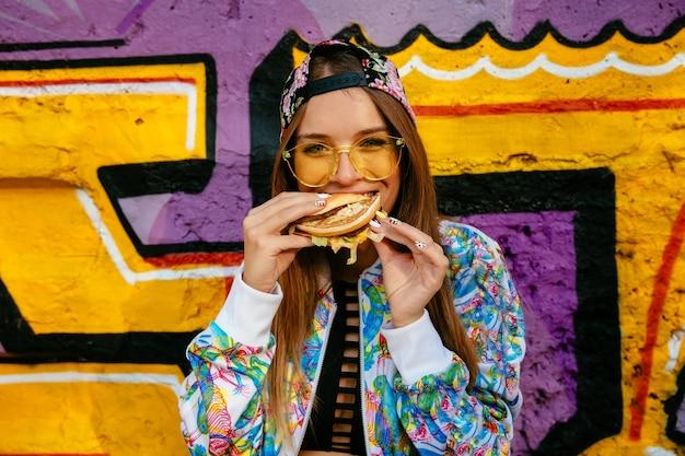 Attraktive junge frau, einen geschmackvollen burger essend. in bunte jacke und mütze gekleidet Kostenlose Fotos
