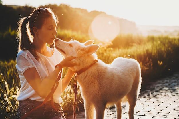 Attraktive junge frau in sommerkleidung mit pferdeschwanz, der mit geschlossenen augen auf pflaster sitzt und nase ihres hundes küsst, der nahe bei sonnenuntergang auf hintergrundbeleuchtung steht Premium Fotos