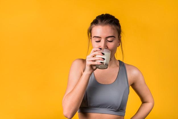 Attraktive junge frau in trinkmilch der sportkleidung Kostenlose Fotos