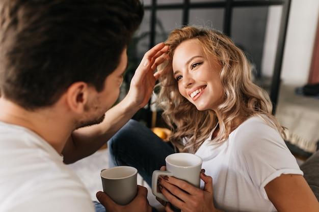 Attraktive junge frau mit blonden haaren, die ihren freund ansieht und lächelt, während er ihre haare repariert. glückliches paar in der liebe, die zeit zu hause zusammen verbringt. Kostenlose Fotos