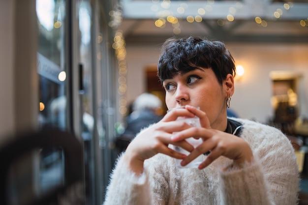 Attraktive junge frau mit kurzen haaren trinkwasser in einem café und blick aus dem fenster Kostenlose Fotos
