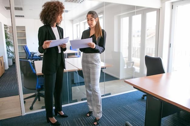 Attraktive junge geschäftsfrauen diskutieren dokumentation in händen. zwei ziemlich selbstbewusste kolleginnen, die papiere halten und im büroraum stehen. teamwork-, geschäfts- und managementkonzept Kostenlose Fotos