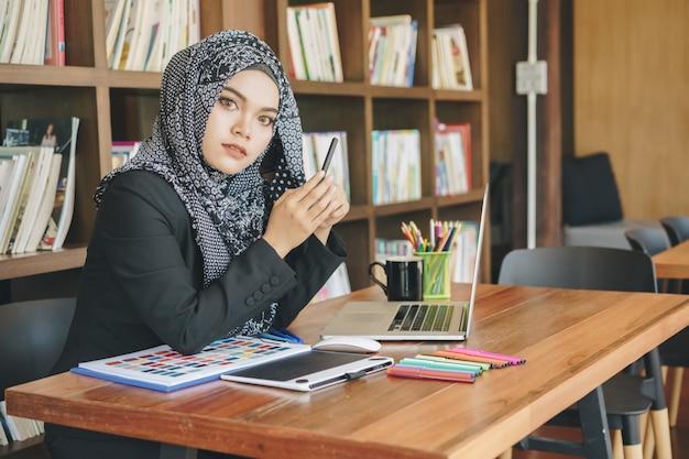 Attraktive junge moslemische kreative designerfrau, die stifttabletts und laptop vor bücherregal verwendet. Premium Fotos