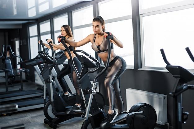 Attraktive junge sportfrau arbeitet in der turnhalle aus. kardiotraining auf dem laufband. laufen auf dem laufband Premium Fotos