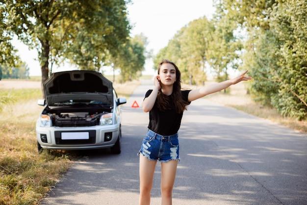 Attraktive junge studentenfrau versucht, passantenauto zu stoppen und um eine hilfe zu bitten, weil ihr auto gebrochen ist Premium Fotos