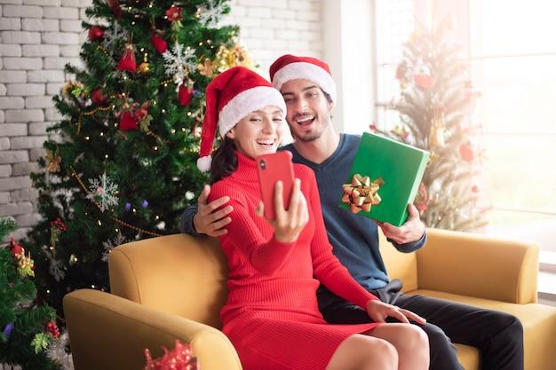 Attraktive kaukasische paare der liebe feiern weihnachten im haus Premium Fotos
