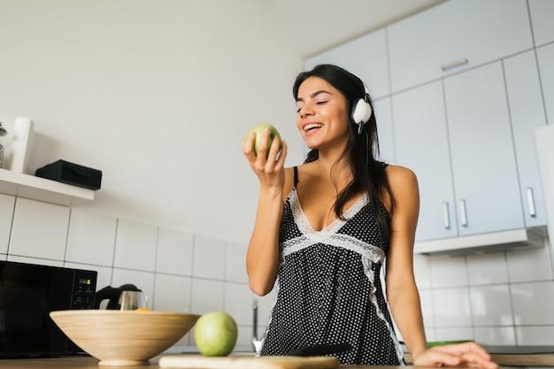 Attraktive lächelnde frau im pyjama beim frühstück in der küche am morgen, gesunder lebensstil, apfel aß, musik auf kopfhörern hörend Kostenlose Fotos