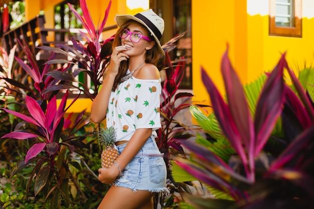 Attraktive lächelnde frau im urlaub in der gedruckten t-shirt-strohhut-sommermode, hände, die ananas halten Kostenlose Fotos