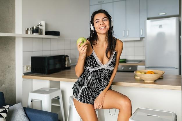Attraktive lächelnde frau in sexy pyjamas, die am morgen in der küche frühstücken, gesunden lebensstil, apfel essen, musik über kopfhörer hören Kostenlose Fotos