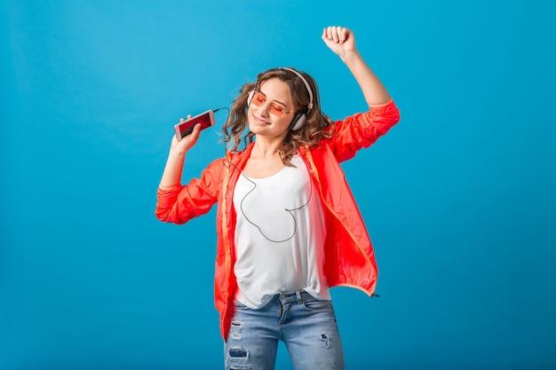 Attraktive lächelnde glückliche frau, die musik hört in den kopfhörern gekleidet im hipster-stil-outfit lokalisiert auf blauem studiohintergrund, trägt rosa jacke und sonnenbrille Kostenlose Fotos