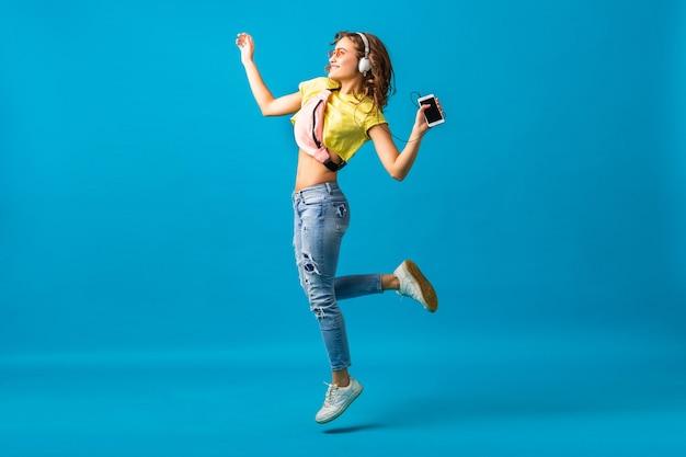 Attraktive lächelnde glückliche frau, die musik hört in den kopfhörern gekleidet im stilvollen hipster-outfit lokalisiert auf blauem studiohintergrund, das bunte kleidung trägt Kostenlose Fotos