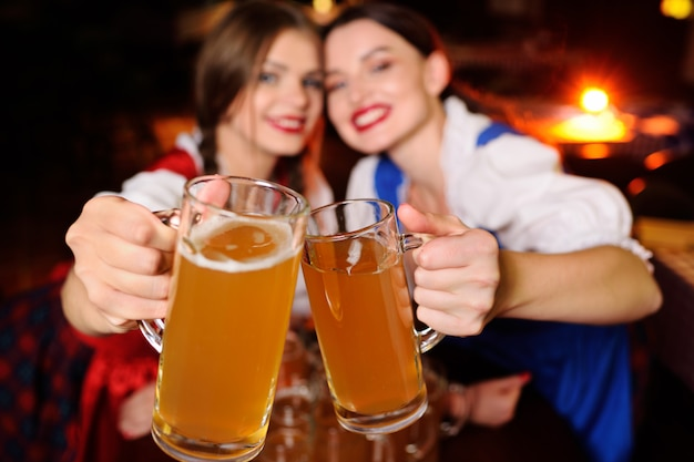 Attraktive mädchen in bayerischen kleidern sitzen an einem tisch in einer bar. Premium Fotos
