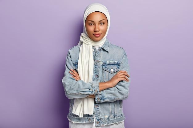 Attraktive östliche frau bedeckt kopf mit weißem kopftuch, um ihre würde und macht zu schützen, hat spezielle kleiderordnung, drückt die hände, sieht bescheiden aus, posiert über lila wand. islamische regeln Kostenlose Fotos