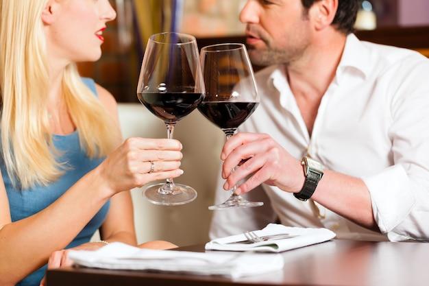 Attraktive paare, die rotwein im restaurant oder in der bar trinken Premium Fotos