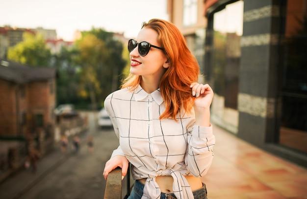 Attraktive redhaired frau in den brillen, die auf weißer bluse tragen Premium Fotos