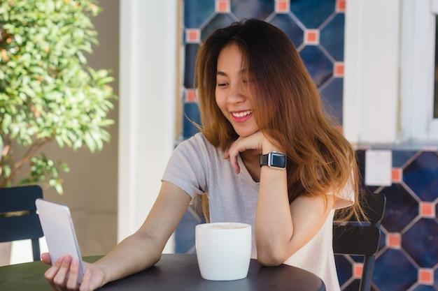 Attraktive schöne glückliche junge asiatin, die ein selfie unter verwendung eines intelligenten telefons am café nimmt Kostenlose Fotos