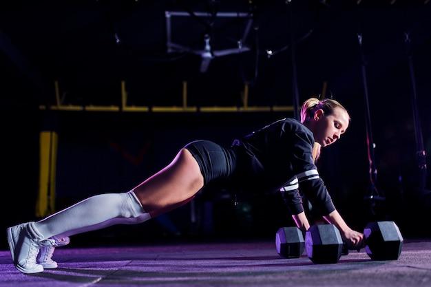 Attraktive sitzmittelalterfrau tut plankenübung beim ausarbeiten in der turnhalle Premium Fotos