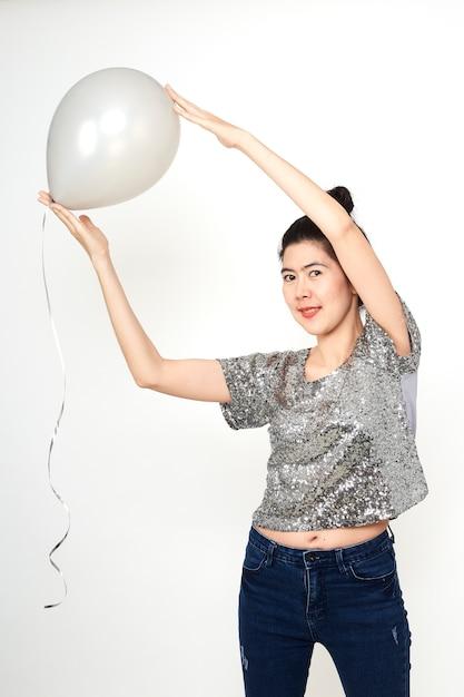 Attraktive stilvolle schöne asiatische frau mit pastellballonen auf weißen hintergründen Premium Fotos