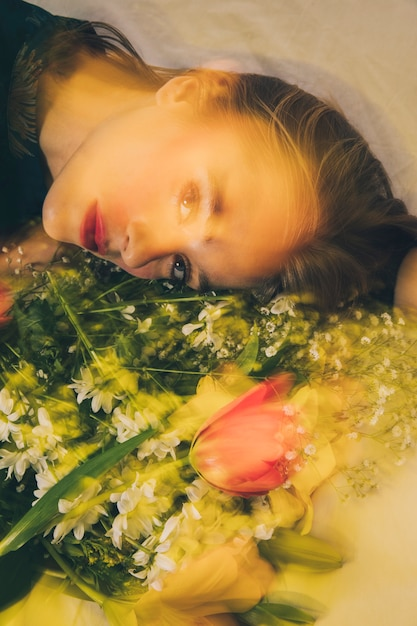 Attraktive träumerische frau, die mit blumenstrauß der blumen liegt Kostenlose Fotos