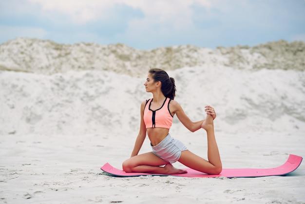 Attraktive und gesunde junge frau, die bei sonnenaufgang übungen am strand macht Premium Fotos