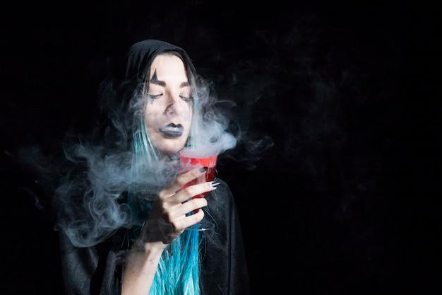 Attraktive zauberin, die becher mit rotem rauchigem alkohol hält Kostenlose Fotos