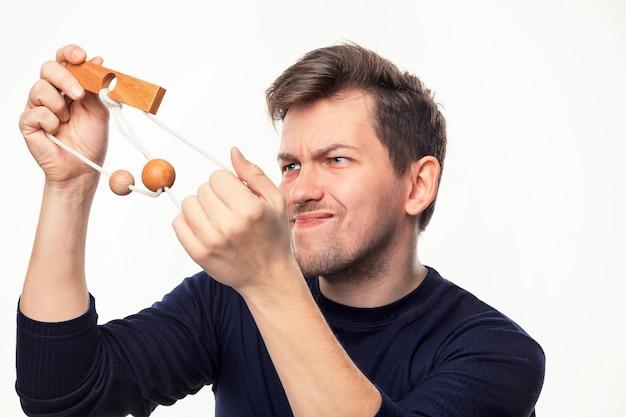 Attraktiver 25-jähriger geschäftsmann, der verwirrt auf holzpuzzle schaut. Kostenlose Fotos