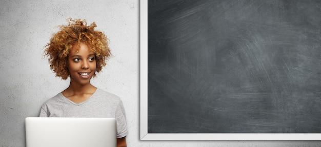 Attraktiver afrikanischer student mit afro-frisur und süßem lächeln, mit nachdenklichem ausdruck beiseite schauend, freie internetverbindung auf laptop-computer verwendend, klassenarbeit machend, an tafel sitzend Kostenlose Fotos