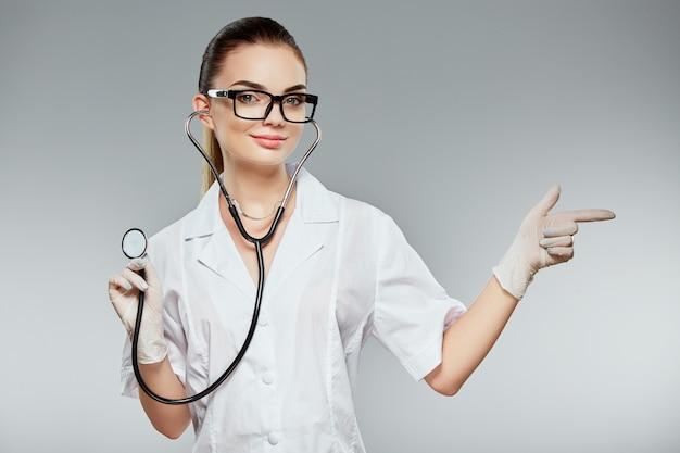 Attraktiver arzt mit braunen haaren und nacktem make-up, der weiße medizinische uniform, brille, stethoskope und weiße handschuhe am grauen studiohintergrund trägt und mit dem finger zeigt. Premium Fotos