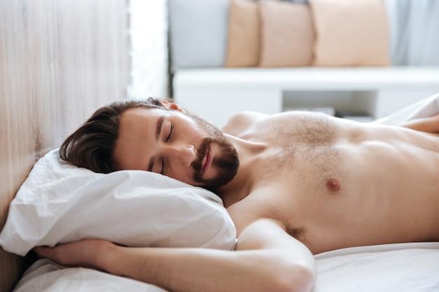 Attraktiver bärtiger junger mann, der im bett schläft Kostenlose Fotos